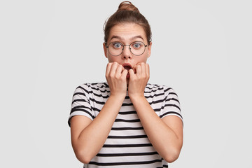 Indoor shot of shocked beautiful female with hair bun and pleasant appearance, looks nervously at camera, feels anxious before important event, wears striped t shirt, isolated on white background