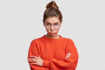 Upset beautiful female with offended look, curves lower lip in dissatisfaction, keeps hands crossed, wears oversized knitted sweater, being abused by close person. People and negative emotions