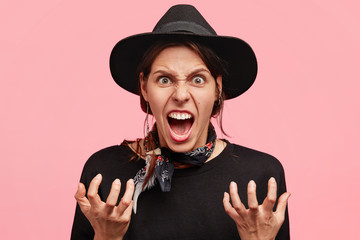 Photo of irritated young female gestures actively with annoyance, being angry and mad, wears fashionable black hat and sweater. Annoyed cowgirl has some problems, shouts at somebody angrily.