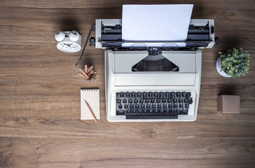 Top view of  old typewriter with blank notepad,alarm clock, houseplant and pencil on a wooden table