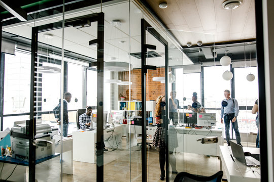 modern bright small office with glass walls, glass door, panorama window and stylish lamps