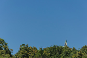 little white bell tower rises above the green trees against the clear blue sky