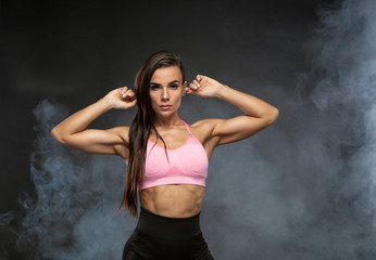 Image of fitness woman in sports clothing in the smoke. Young female model with muscular body.