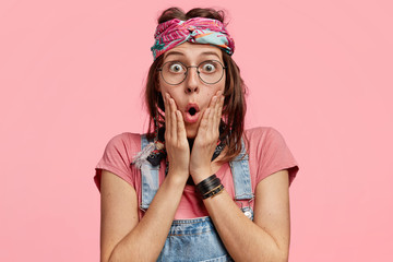 Portrait of stunned adorable hippie woman, has shocked expression as recieves shocking news, keeps mouth rounded, isolated over pink background. Woman belongs to hippy subculture. Emotions concept