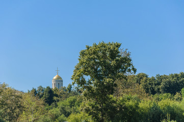 Orthodox Church with Golden dome and a cross rises above the trees on the background of clear blue sky. Vladimir city