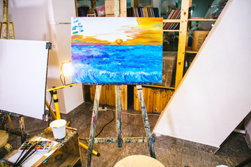 Amatur oil painting on canvas in workshop. Painting of evening sunset sky over the ocean