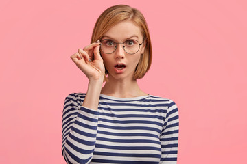 Indoor shot of amazed beautiful young female worker, wears striped sweater and round glasses, being shocked to recieve difficult task, looks scrupulously, poses against pink studio background