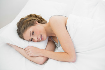 Smiling calm woman lying under the cover on her bed