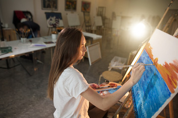 Young amateur woman drawing her first picture with oil paints in dark workshop with flash light