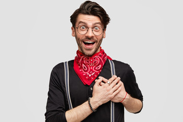Cheerful overjoyed hipster with dark stubble and trendy hairdo, exppresses his amazement and thankfulness, keeps hand on heart, has excited expression, poses indoor. People, human emotions concept
