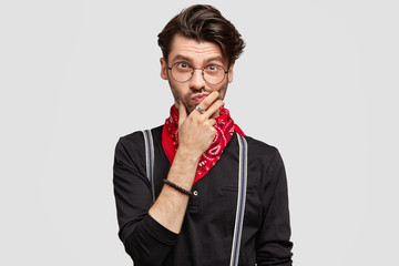 Shot of hesitant male model has stubble, keeps chin and looks with uncertain thoughtful expression, wears trendy black shirt with braces and red bandana on neck, tries to understand something