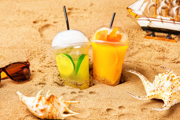 Two glasses of fresh cocktails at yellow beach sand with seashells and footprints at background.