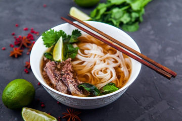 Vietnamese Pho Noodle Soup. Beef with Chilli, Basil, Rice Noodles, Bean Shoots showing noodles