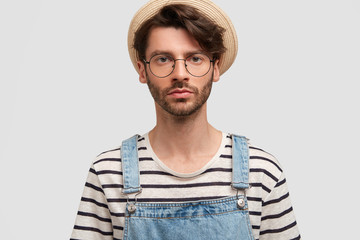 Serious bearded young male farmer looks confidently at camera, wears countryside casual clothes, poses against white studio background. People, farming, agriculture and facial expressions concept