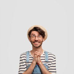 Vertical shot of happy male farmer makes praying gesture, asks God for good weather on tomorrow`s day as going to reap harvest, looks with great desire upwards, blank copy space for promotional text
