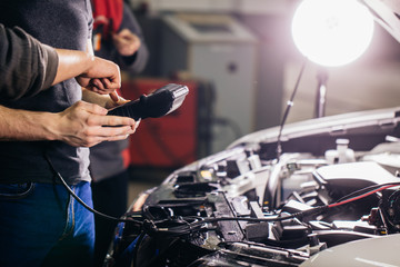 Car mechanic using electrical tool for testing car system in garage repair