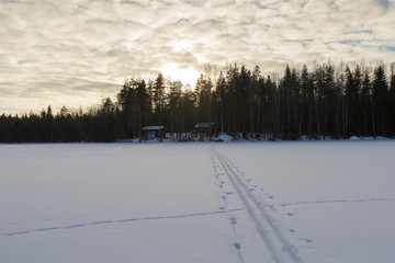 Ski tracks on the deep snow on the lake ice during sunset. Snow is glowing due to sun going down.
