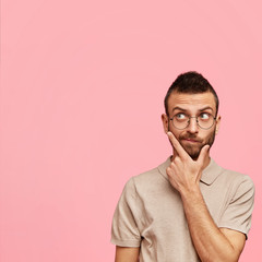 Vertical shot of pensive bearded young male holds chin and contemplates about something, wears round spectacles and t shirt, poses against pink background with copy space for your advertisement