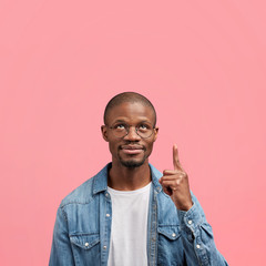 Photo of confident bald black African American middle aged male in fashionable denim shirt, shows something upwards, attracts your attention at blank copy space for promotional text or hearder