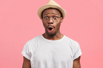 Portrait of stunned African American adult looks with amazed expression, being shocked to have spoiled vacation, poses against pink background. Surprised dark skinned male wears casual clothing