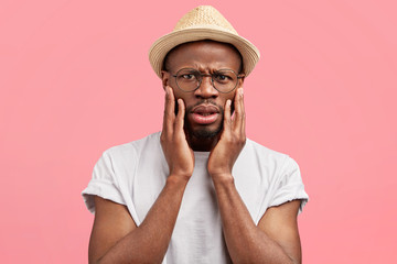 Photo of discontent African American guy looks with angry sullen expression, keeps hand on cheeks, being shocked with negative news, wears casual hat and t shirt, isolated over pink background