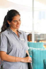 The waitress takes the customer's order in the hotel restaurant. Morning time. The girl is smiling. A waiter woman takes an order holding the tray by hand. The concept of service.