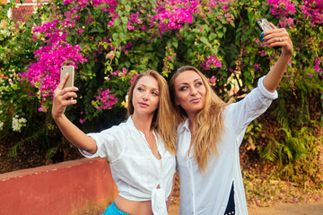two women do selfie on a background of a floral wall