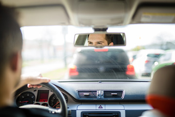 Man looking in rear view mirrow while driving