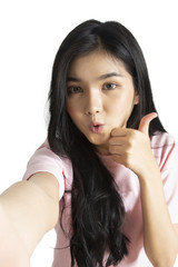 Asian girl taking selfie photo while makinging funny face and took her thumb up.