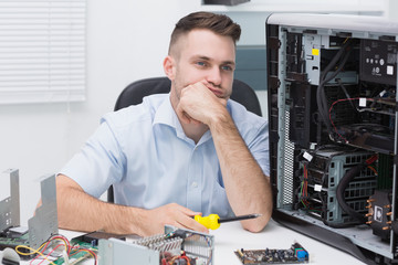 Thoughtful hardware professional sitting by an open cpu