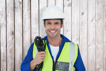 Confident electrician with wire against white background against digitally generated grey wooden planks