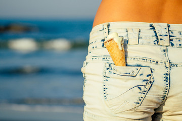 soft ice cream melts in pocket shorts on the beach