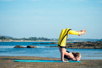 beautiful and flexible woman practicing yoga on the beach