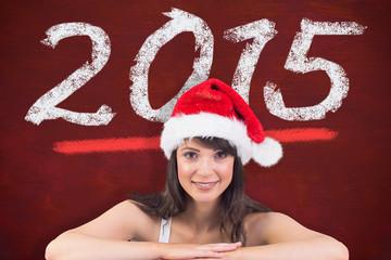Festive brunette leaning on large poster against desk