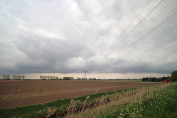 Wide angle view of field which have been ploughed after harvest of tulip bulbs with dark clouds.