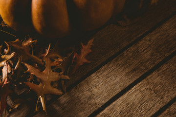 Cropped image of pumpkin with autumn leaves on table