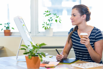 Smiling casual businesswoman working on digitizer and holding coffee