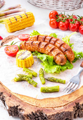 grilled krakauer sausage with boiled corn and green salad