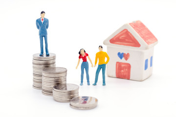 Miniature businessman standing on coins and the house behind. saving and loan concept.