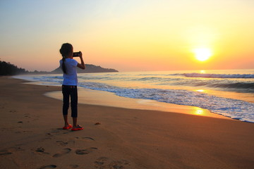 Little girl taking photos on the beach Kid girl on the beach with phone taking photos of a seascape view. child is making selfie on a sunset ,Thailand