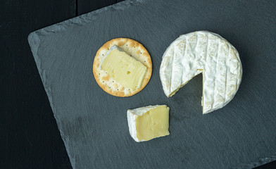 Cheese board with brie and cracker on black slate - Camambert type cheese on black background with space for text