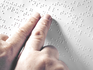 Hands of a blind person reading some braille text touching the relief. Horizontal