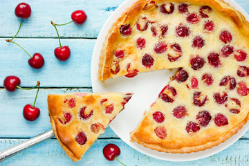 Clafoutis with cherry on a blue wooden background