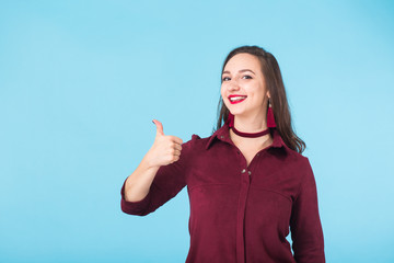Cheerful young brunette caucasian student girl showing thumbs up on blue background with copy space