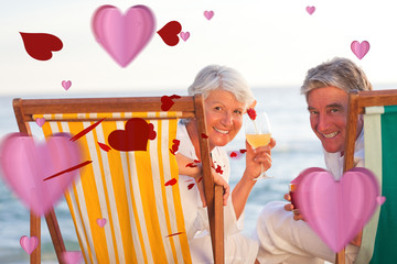 Senior couple drinking a cocktail against love heart pattern