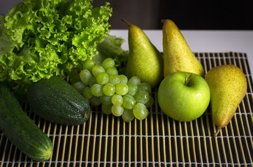 Green healthy vegetables and fruits on a black slates