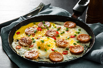fried eggs with sausage and cheese in a frying pan on wooden table