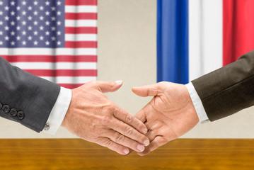 Vertreter der USA und Frankreichs reichen sich die Hand