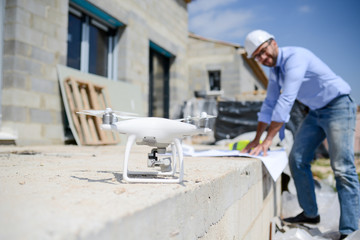 handsome architect flying inspection drone for aerial view of a house construction site industry
