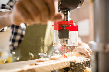 Close up modern artisan using drilling unit boring into piece of wood  with sawdust and woodchips flying off, copy space